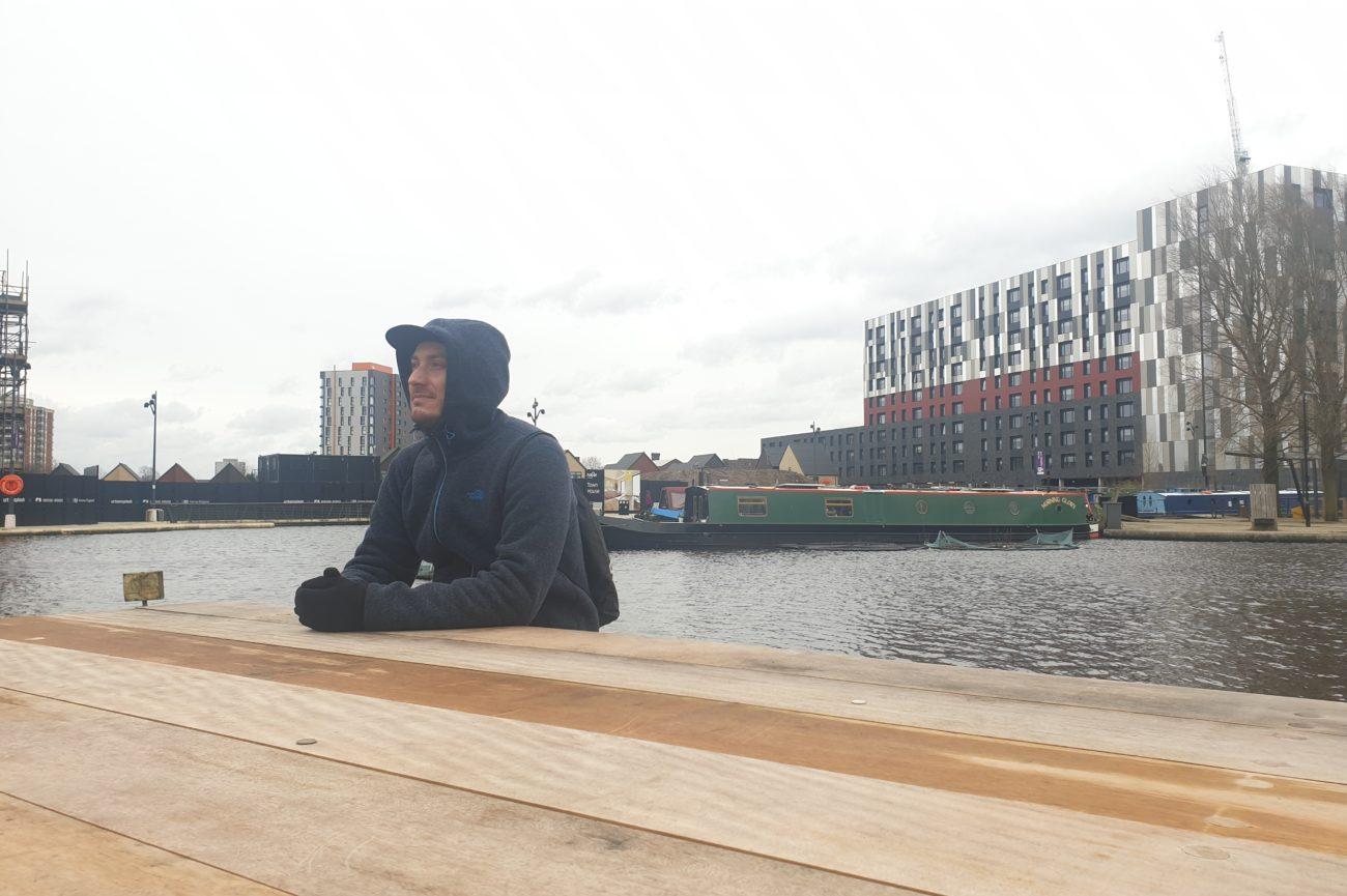 Marco Armana seduto su una panchina di legno. Sullo sfondo un Canale di Manchester