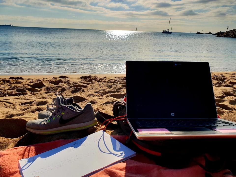 Spiaggia, mare, computer aperto e scarpe da ginnastica