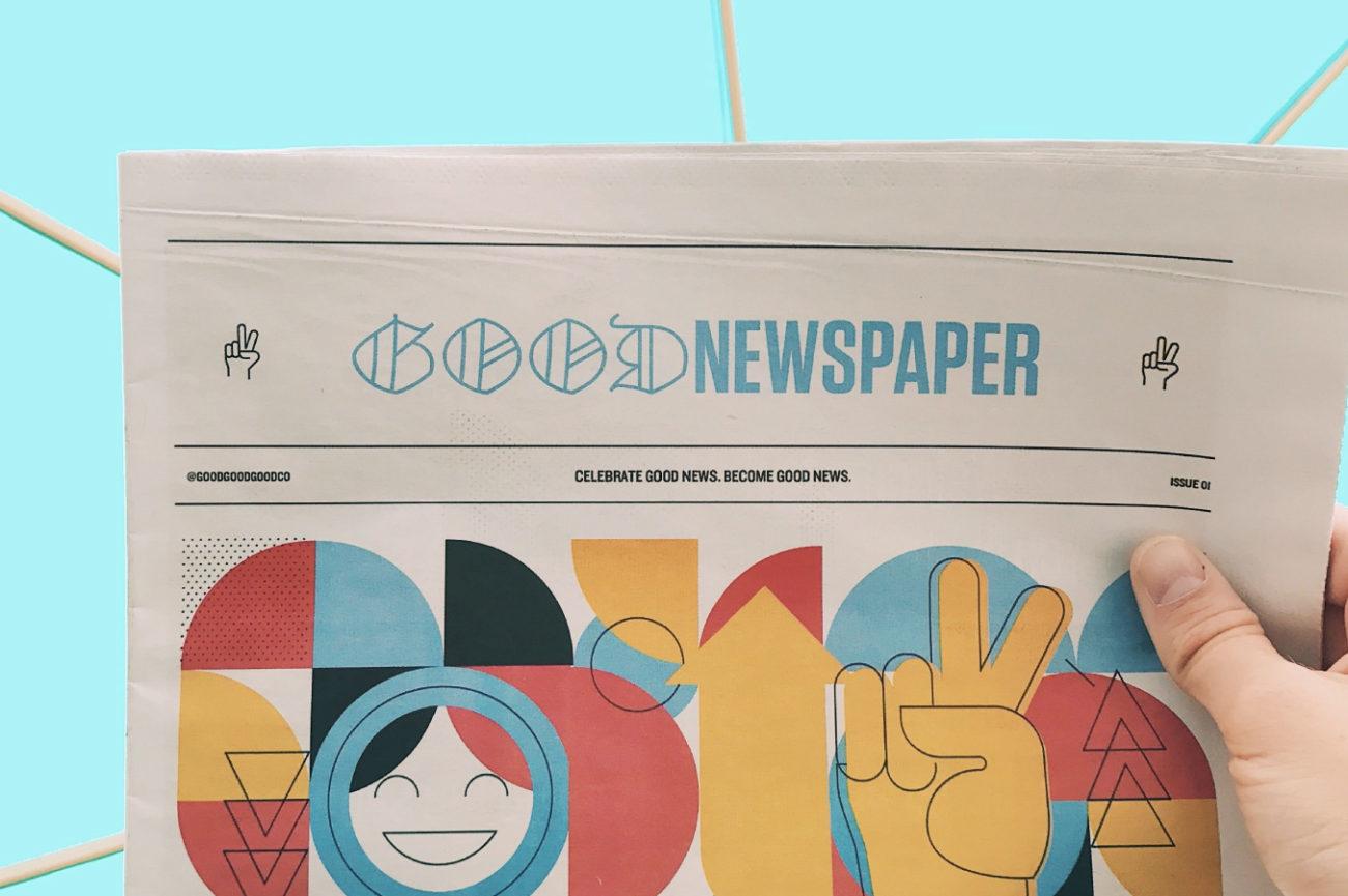 Giornale intitolato Good News tenuto in mano su uno sfondo colorato turchese